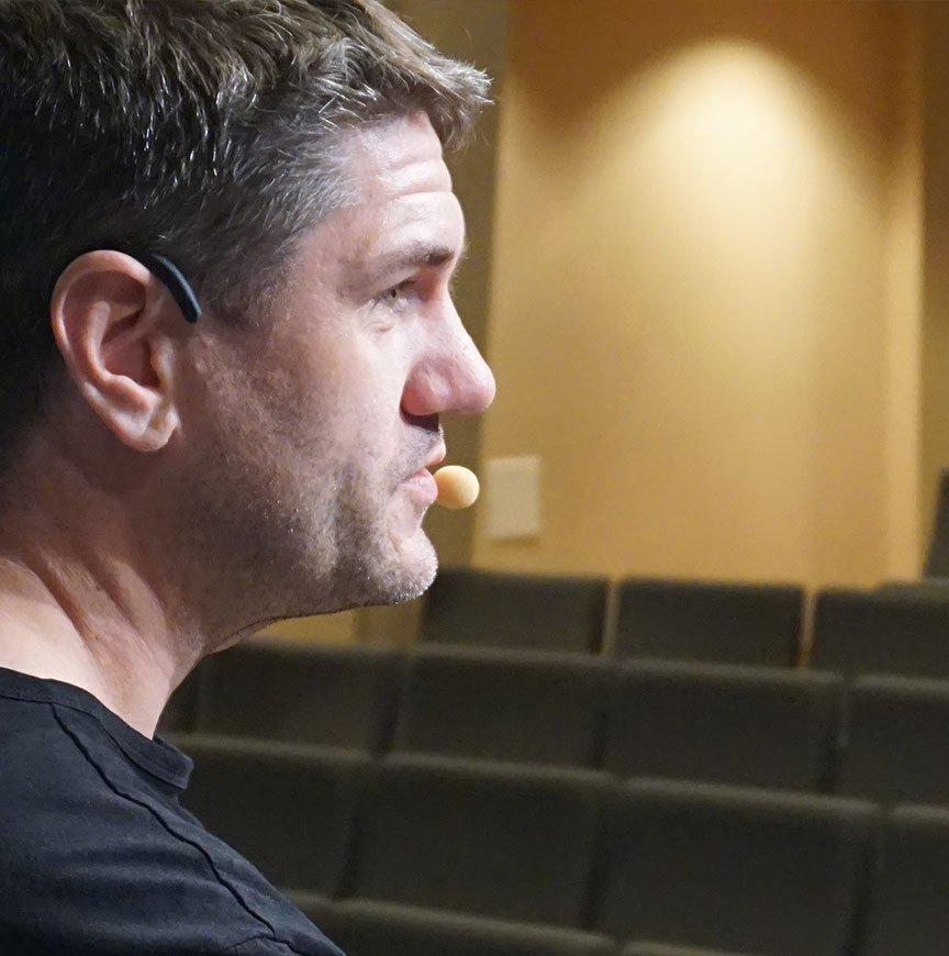 Mikael Reijer i profil talar i mikrofon